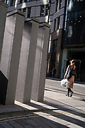 A businesswoman walks past modern pillar architecture in the City of London, the capital's financial district, on 21st October 2021, in London, England.