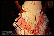 Detail of woman's hands on traditional ruffly dress at sunset; Feria de Abril, Seville. Spain