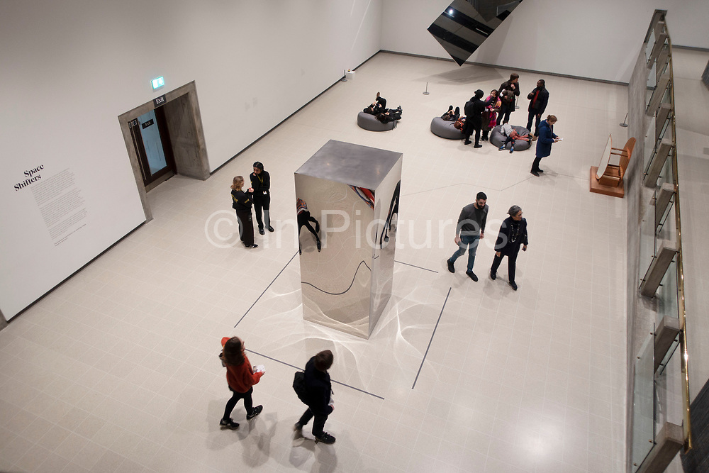 Visitors interacting with artworks at the Space Shifters exhibition at the Hayward Gallery on 16th December 2018 in London, United Kingdom. The exhibit was a major group show of sculptures and installations that explored perception and space, featuring 20 artists. Non-Object Door, 2008, by Anish Kapoor.