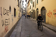 A female Italian cyclist pedals along a graffiti-lined street near Florence's Piazza Santa Croce. With the words 'I Love Weed' that refers to the popularity and merits of cannabis, the graffiti of other tags and assorted writings can be seen stretching into the distance where a family have passed-by and are continuing their journey towards their home to the east of the city.