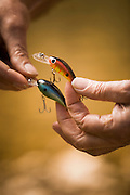 Hands tying fishing lure.