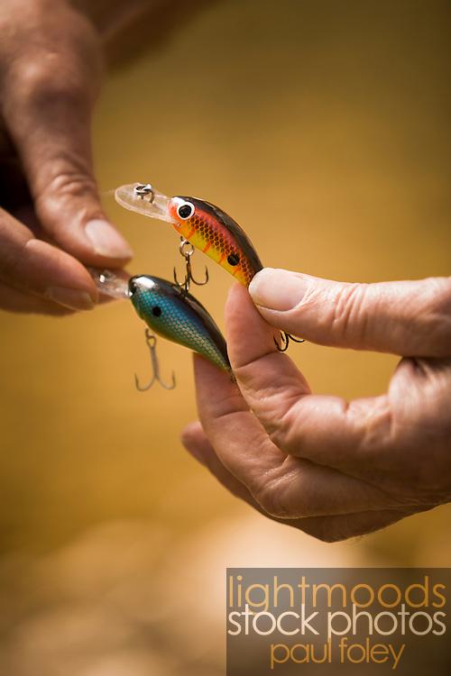Hands tying fishing lure.