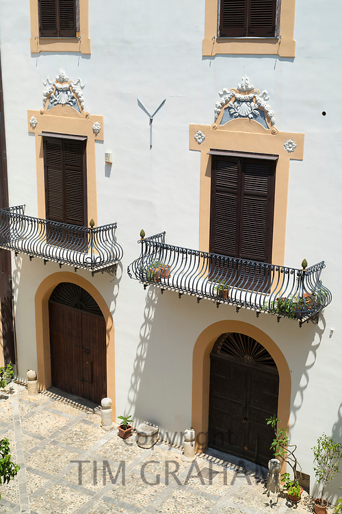 Typical Sicilian palazzo courtyard and ornate architecture with cast iron balcony and old stone paving in the city of Palermo, Sicily, Italy