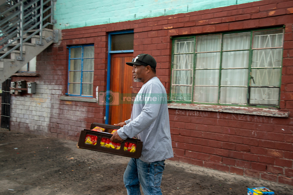 """A community marshall receives bread delivered by volunteers to the community of Parkwood, a subburb of Cape Town, located on the Cape Flats, Monday, April 20, 2020. The majority of the people who live here are unemployed during """"normal"""" circumstances. And as South Africa is now in lockdown due to the Coronavirus, many of those who had jobs have also lost their income. So many people are starving. The feeding scheme is a joint community effort, paid for solely by donations from the public to feed more than 3,000 households. The group is also receiving transportation support by The South African Red Cross Society. PHOTO: EVA-LOTTA JANSSON"""