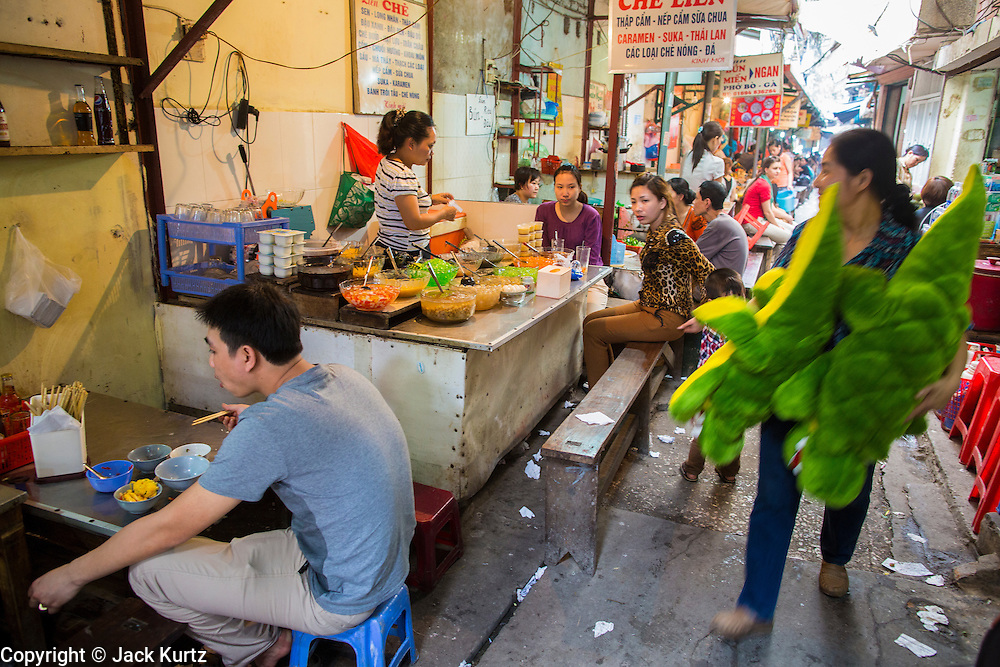 05 APRIL 2012 - HANOI, VIETNAM: A woman carries a stuffed alligator toy down an alley lined with food stalls in Hanoi, the capital of Vietnam.   PHOTO BY JACK KURTZ
