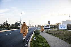 October 27, 2016 - Calais, France - Two refugees leave the hangar distribution of refugees into the jungle with a blanket on the back, in Calais, October 27, 2016..The Calais jungle begins its fourth day of dismantling. Most refugees have left the jungle. Some roam the jungle and over 100 young refugees have no place in the Provisional Home Centre. The workers are destroying the jungle growing rapidly. (Credit Image: © Julien Pitinome/NurPhoto via ZUMA Press)