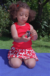 Young girl kneeling on picnic blanket in garden playing with toy truck,