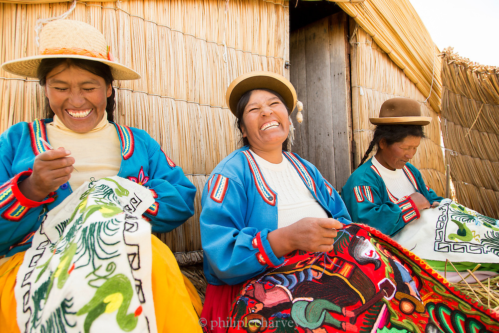 Native Uru women doing embroidery on the Floating islands of Lake Titicaka, Puno, Peru, South America