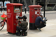Camera operators during filming in the City fo London hide behind post boxes on 2nd July 2021 in London, United Kingdom.
