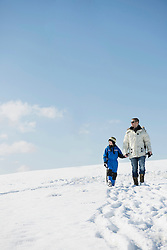 Father and son walking in winter, Bavaria, Germany