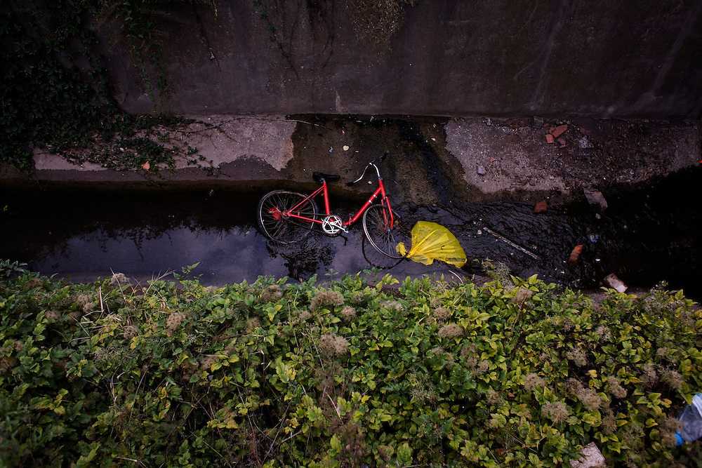 A discarded bicycle in a water run-off near the Rakovica Roma camp.