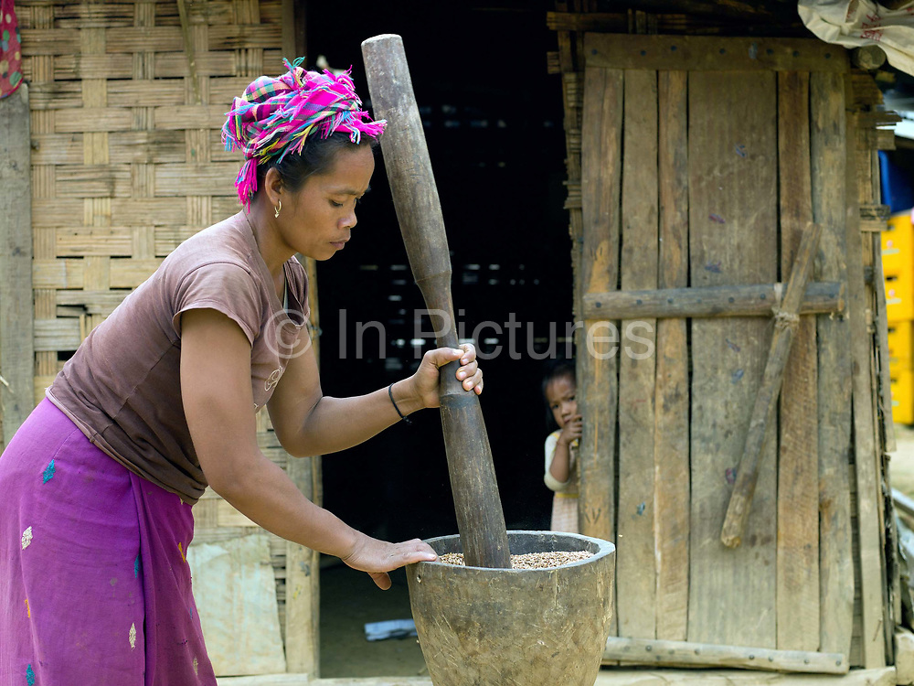 A Khmu ethnic minority woman pounds sticky rice with a traditional wooden mortar and pestle outside her home in Ban Pakpok, Phongsaly province, Lao PDR. Her family have recently moved from their remote mountain village to the riverside village of Ban Pakpok which is located on a road nearby Nam Ou Cascade Hydropower Project Dam 5 construction site.