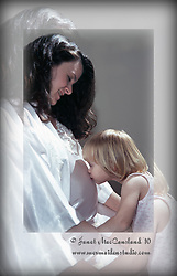An expectant mother is kissed on her pregnant belly by her first born daughter. A special repeating border has been created around the central portrait.