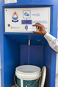 People using a water ATM in Raj Nagar in Dwarka. The solar powered vending machines installed by a for-profit social enterprise called Piramal dispense clean drinking water via a pre-paid smartcard to residents who have no access to water on tap in their homes. New Delhi, India