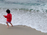 A little child running away from the water.