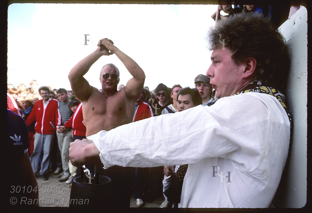 Young men test strength by holding weight at arm's length during summer festival in Thjorsardalur Iceland