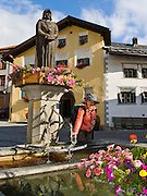 """A traveler fills a water bottle at a fountain decorated with statue and flowers, in Scuol, Engadine, Switzerland, the Alps, Europe. Scuol (or Schuls) is the terminal station of the """"Rätische Bahn"""" (RhB), at 1244 meters or 4081 feet elevation in Graubünden canton. The Swiss valley of Engadine translates as the """"garden of the En (or Inn) River"""" (Engadin in German, Engiadina in Romansh, Engadina in Italian). Published in Ryder-Walker Alpine Adventures """"Inn to Inn Alpine Hiking Adventures"""" Catalog 2006, and in Wilderness Travel Catalog of Adventures 2014."""