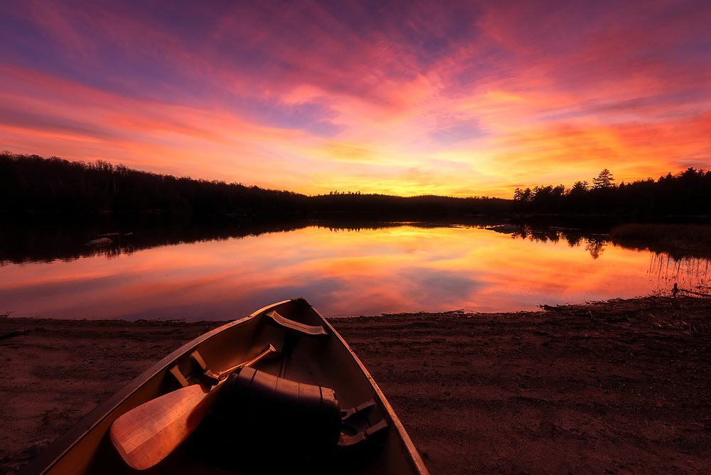 Canoe and paddle on beach during sunset with reflection on Sunday Lake in Ontario, Canada on November 7, 2020.<br /> <br /> PHOTO: Steve Kingsman / Steve Kingsman Photography