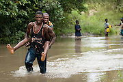 A man carries another on his back across an overflowing river near the town of Amakpa, Benin on Tuesday September 18, 2007.