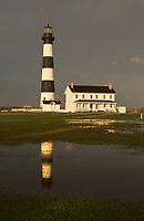 NC01299-00...NORTH CAROLINA - The sun comes out in the late afternoon after a very wet day at Bodie Island Lighthouse reflecting in a puddle; part of Cape Hatteras National Seashore.