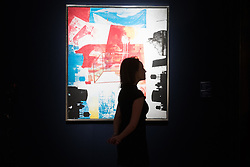 Christie's, London, March 3rd 2017. PICTURED: A woman passes Robert Rauschenberg's 'Transom', oil and silkscreen ink on canvas, painted in 1963, which is expected to fetch between £4-6 million. Fine art auctioneers Christies hold a press preview for their Post-War and Contemporary Art auctions to be held on March 7th and 8th.