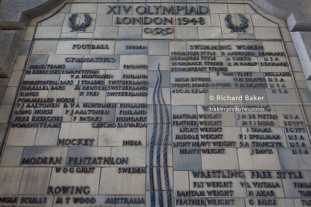 A detail of one of two panels commemorating the names of international athletes who won gold medals at the London Olympics held at the old Wembley Stadium in 1948, on 6th November 2019, in Wembley, London, England. The fragile and heavy panels were carefully removed when the old stadium was demolished in 2000 and restored when the new structure was completed, in memory of the post-war (austerity) games.