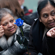 The funeral of former Prime Minister Margaret Thatcher who died Monday April 8. Two Asian women with a blue rose wait for the funeral procession to arrive.