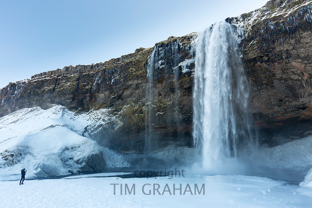Tourist taking photograph at spectacular waterfall Seljalandsfoss in South Iceland