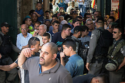 © Licensed to London News Pictures . 05/06/2016 . Jerusalem , Israel . Soldiers separate residents of the Old City's Muslim district from thousands of Jews with flags processing through the Old City's Muslim district , on the way to the Western Wall . Israeli Jews celebrate Jerusalem Day . Photo credit : Joel Goodman/LNP