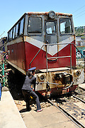 Female guard adjusting the coupling on a very old diesel locomotive. Da Lat Railway Station, Da Lat, Vietnam