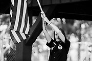 09252016 - Madison, Indiana, USA: A member of the Baltimore-based Confederate White Knights of the Ku Klux Klan holds the American flag during a rally in Madison, Ind. The Klansmen were outnumbered by protesters.