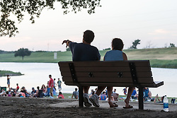 Couple on bench overlooking river at the Panther Island Pavilion, Trinity River, Fort Worth, Texas, USA.