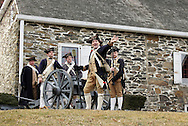 Newburgh, New York - Revolutionary War reenactors in uniforms prepare to fire a cannon at Washington's Headquarters State Historic Site as part of George Washington's birthday celebration on Feb. 18, 2012. The reenactors are from John Lamb's Artillery Company. Their cannon is modeled on the British three-pounder field piece. Hasbrouck House, the longest-serving headquarters of Washington during the American Revolution, is in the background.