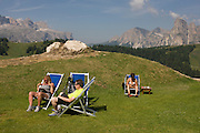 Sunbathing hikers in deckchairs in the Pralongià above San Cassiano-St. Kassian in the Dolomites, south Tyrol, northern Italy. In winter, the Pralongià meadows are the heart of Alta Badia's skiing area.