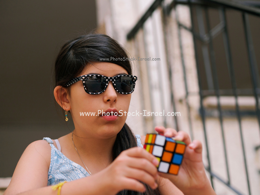 young preteen girl with sunglasses attempts to solve Rubik's Cube