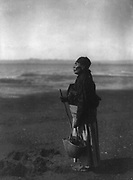 American Indian woman standing holding basket on beach, c1910.  Photograph by Edward Curtis (1868-1952).