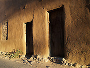 Two rustic doors to an ancient adobe building next to the San Miguel Mission in Santa Fe, New Mexico.