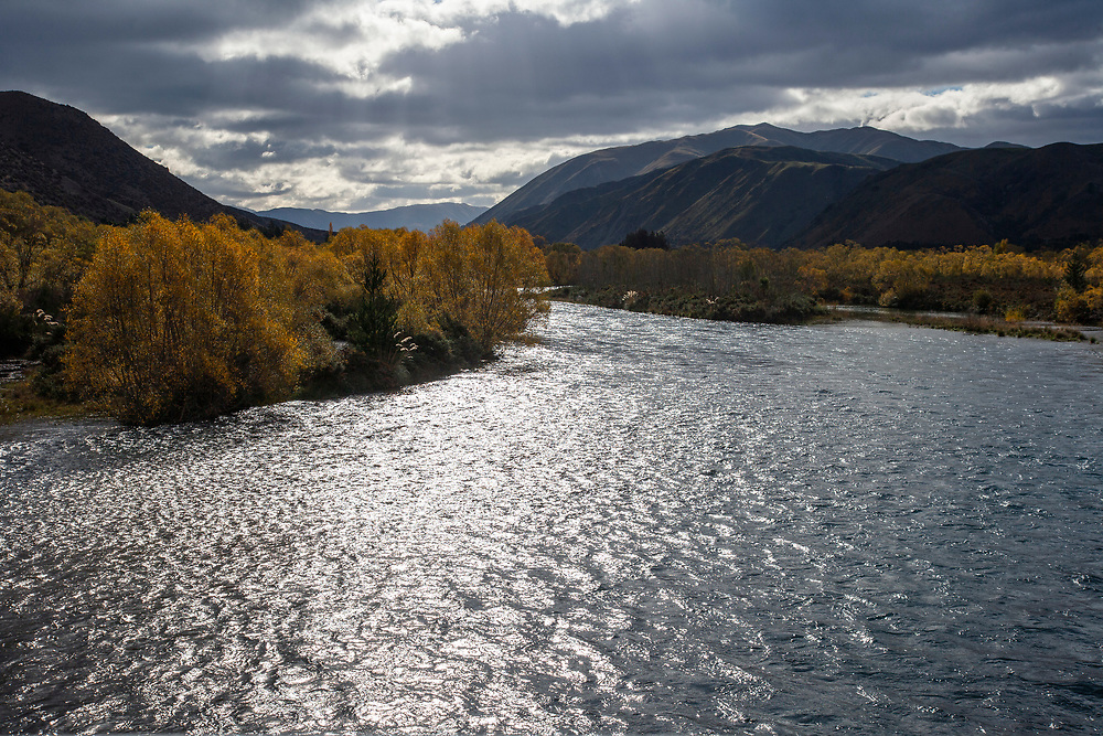 View over the glistening Hakataramea River with autumn trees in the background