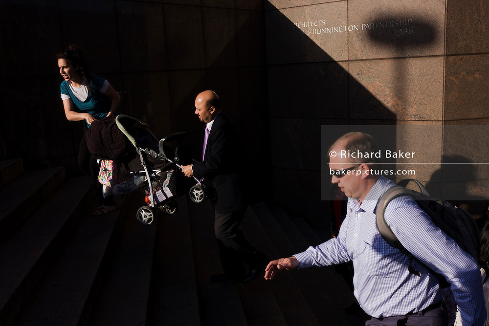 Surrounded by deep shadows, a commuter helps a mother with a buggy up the steps of number 1 London Bridge.