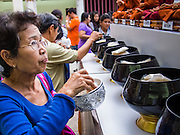 16 NOVEMBER 2013 - BANGKOK, THAILAND: People make merit by donating rice to Wat Saket during the annual temple fair. Wat Saket is on a man-made hill in the historic section of Bangkok. The temple has golden spire that is 260 feet high which was the highest point in Bangkok for more than 100 years. The temple construction began in the 1800s in the reign of King Rama III and was completed in the reign of King Rama IV. The annual temple fair is held on the 12th lunar month, for nine days around the November full moon. During the fair a red cloth (reminiscent of a monk's robe) is placed around the Golden Mount while the temple grounds hosts Thai traditional theatre, food stalls and traditional shows.  PHOTO BY JACK KURTZ