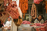 Butchers wait for customers, surrounded by meat, hanging sausages and cow heads, from their stalls at La Merced market in Mexico City, Mexico on June 20, 2008.
