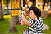 07 JULY 2011 - BANGKOK, THAILAND:   Women exercise early in the morning with large swords in Lumphini Park in Bangkok. Lumphini Park (also Lumpini or Lumpinee) is a 360-rai (57.6-hectare or 142-acre) park in Bangkok, Thailand. The park offers open public space, trees and playgrounds in the Thai capital and contains an artificial lake where visitors can rent a variety of boats. Paths around the park totalling approximately 2.5 km in length are a popular area for evening joggers. Lumpini Park was created in the 1920s by King Rama VI on royal property. A statue of the king stands at the southwestern entrance to the park. It was named for Lumbini, the birthplace of the Buddha in Nepal, and at the time of its creation stood on the outskirts of the city. Today it lies in the heart of the main business district and is in the Lumphini sub-district, on the north side of Rama IV Road, between Ratchadamri Road and Witthayu (Wireless) Road.       PHOTO BY JACK KURTZ