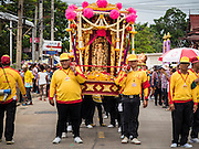 "23 JUNE 2015 - MAHACHAI, SAMUT SAKHON, THAILAND: Men carry the City Pillar Shrine through town during the procession for the shrine in Mahachai. The Chaopho Lak Mueang Procession (City Pillar Shrine Procession) is a religious festival that takes place in June in front of city hall in Mahachai. The ""Chaopho Lak Mueang"" is  placed on a fishing boat and taken across the Tha Chin River from Talat Maha Chai to Tha Chalom in the area of Wat Suwannaram and then paraded through the community before returning to the temple in Mahachai.   PHOTO BY JACK KURTZ"