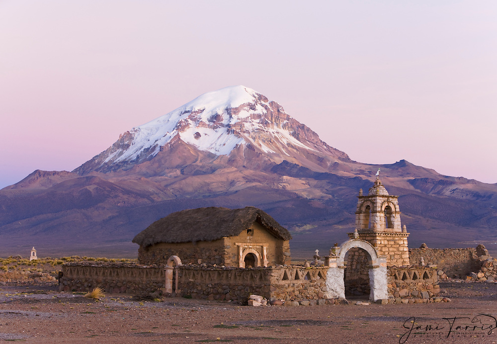 An old Andean church at sunrise  in front of volcanos Parinacota and Sajama on the Altiplano , Bolivia