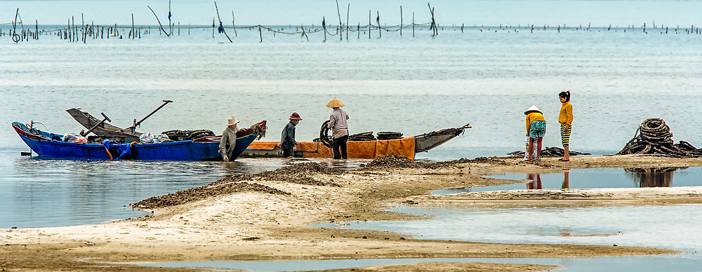 Reclamation:  People unload their boats of the discarded tires they have reclaimed, South of Hue Vietnam.