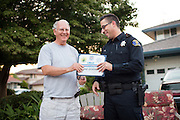 Milpitas resident Mike Queenan accepts a Certificate of Appreciation from Milpitas Police Officer Jason Speckenheuer during a National Night Out event on Sark Court in Milpitas, California, on August 7, 2014. (Stan Olszewski/SOSKIphoto)