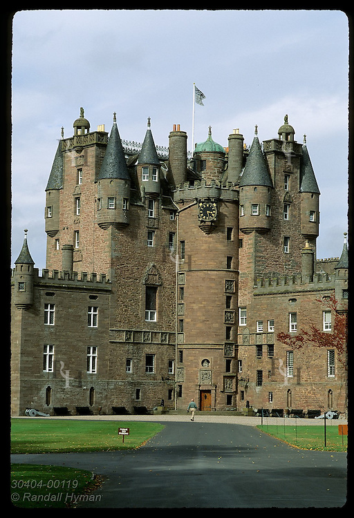 Man walks path in front of Glamis Castle, childhood home of the Queen Mother;  Glamis, Angus, Scotland.