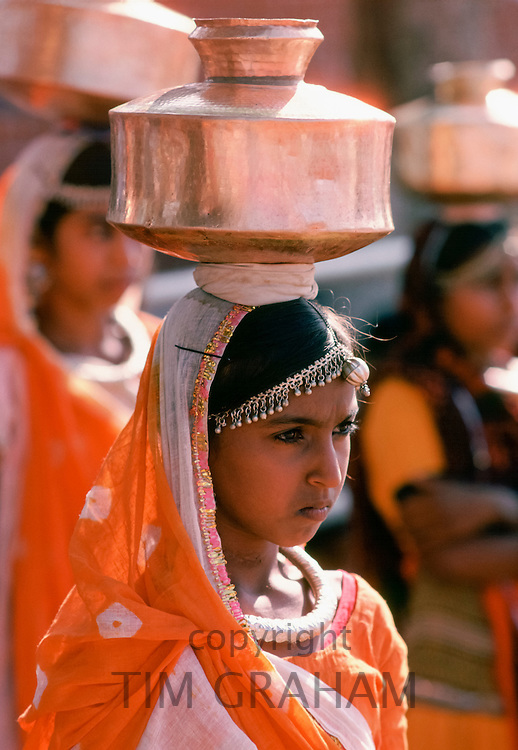 Young Indian women carrying water vessels in street in India