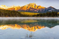 Alpenglow kisses the top of Pyramid Peak at sunrise at Patricia Lake in Jasper  National Park