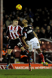 Bristol City's Tyrone Barnett challenges Brentford's Jake Bidwell to the ball in the air - Photo mandatory by-line: Dougie Allward/JMP - Tel: Mobile: 07966 386802 28/01/2014 - SPORT - FOOTBALL - Griffin Park - Brentford - Brentford v Bristol City - Sky Bet League One
